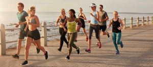 אנשים רצים לאורך טיילת אל מול הים